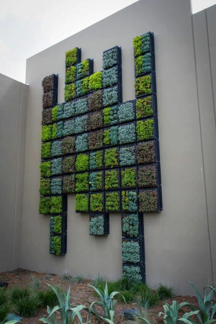 culture verticale sur une cloison de jardin en couleur blanc crème, composition de multiples panneaux de petite taille avec des plantes dans différentes nuances du vert, mur vegetal en palette,mur végétalisé