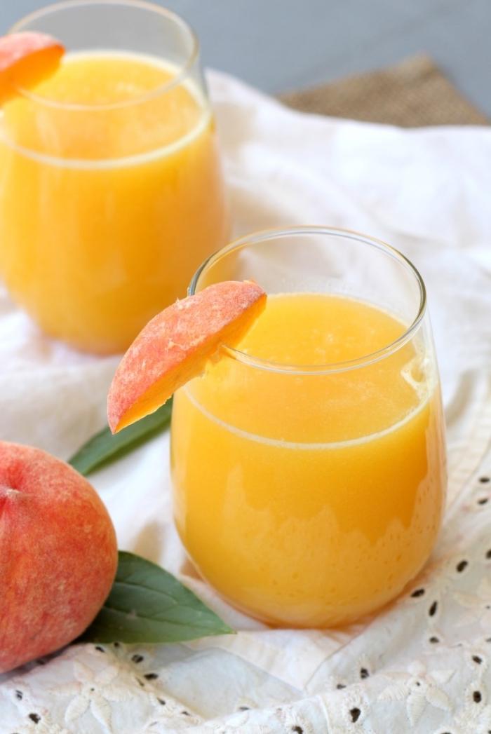 recette jus de fruit facile à préparer soi-même, verre cocktail rempli de jus de pêche et eau froide garni avec tranches de fruit