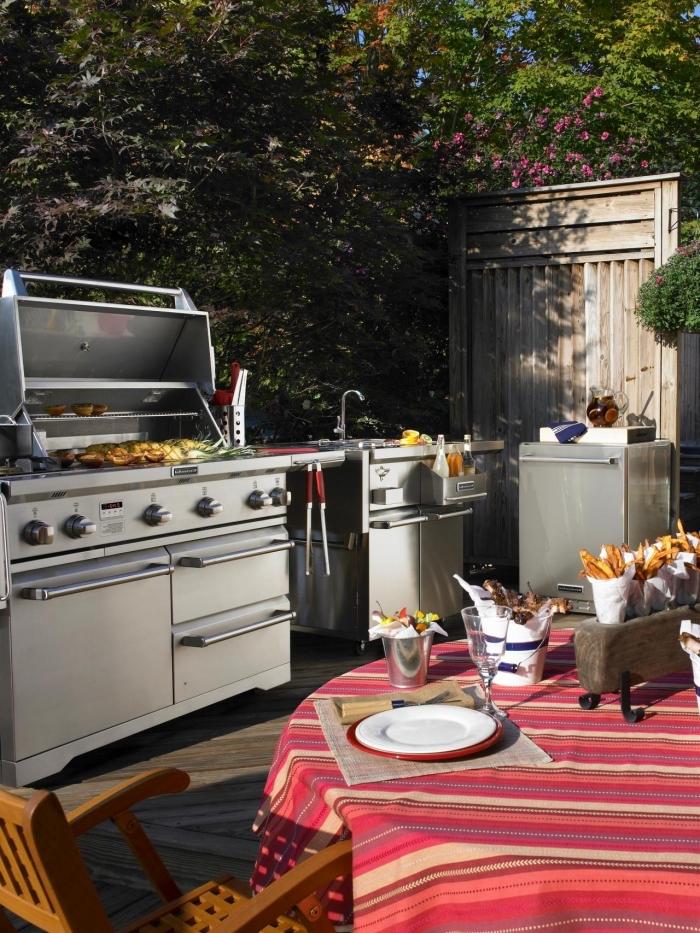 décoration de jardin avec cuisine équipée en barbecue et évier extérieur, comment arranger une table ronde avec nappe rouge