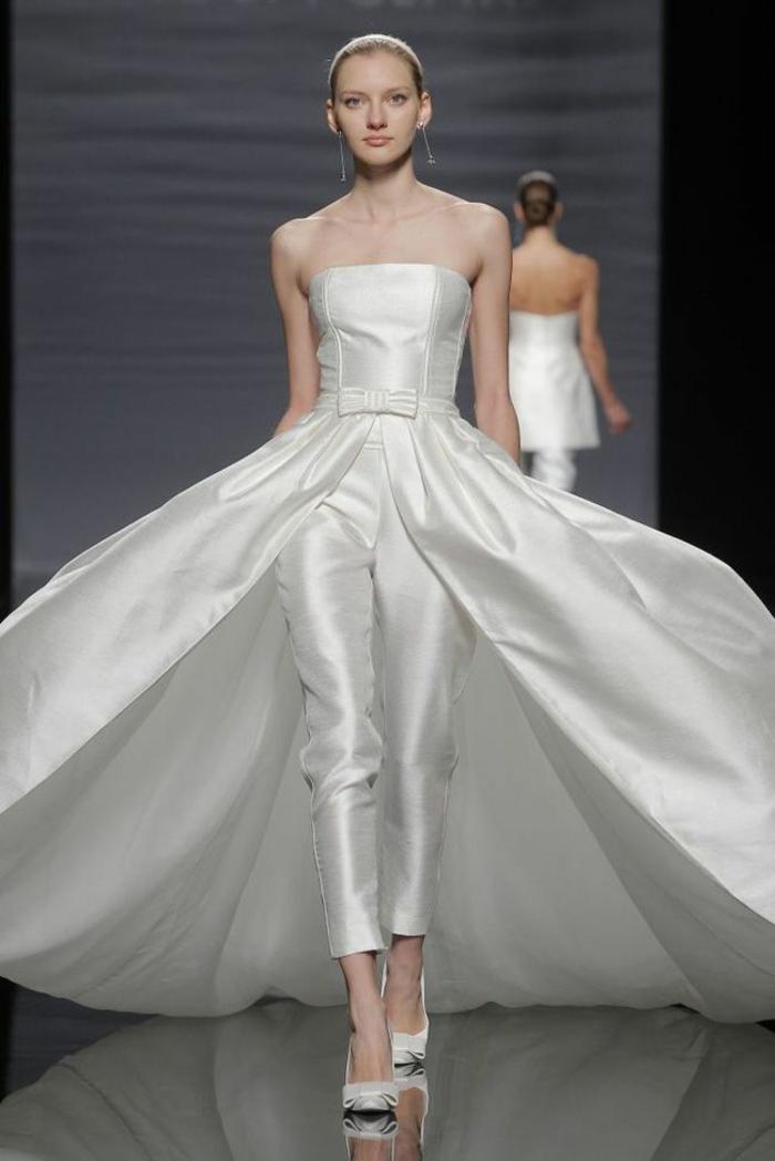 tenue ceremonie femme en tissu blanc satiné, combishort avec bustier, taille sublimée par une ceinture en tissu avec un nœud papillon, pantalon longueur aux chevilles, traîne volumineuse en satin blanc, effet d'ailes durant la marche