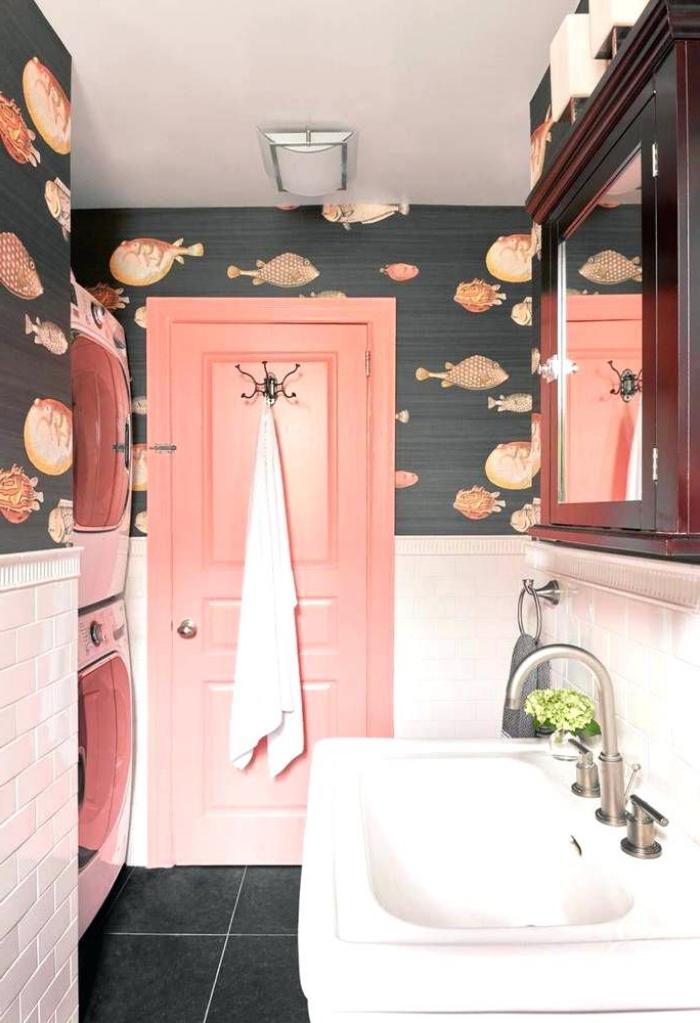 une salle de bains vintage remis au goût du jour grâce à la combinaison inattendue d'un papier peint motif poissons et d'une porte interieur bois avec le carrelage métro
