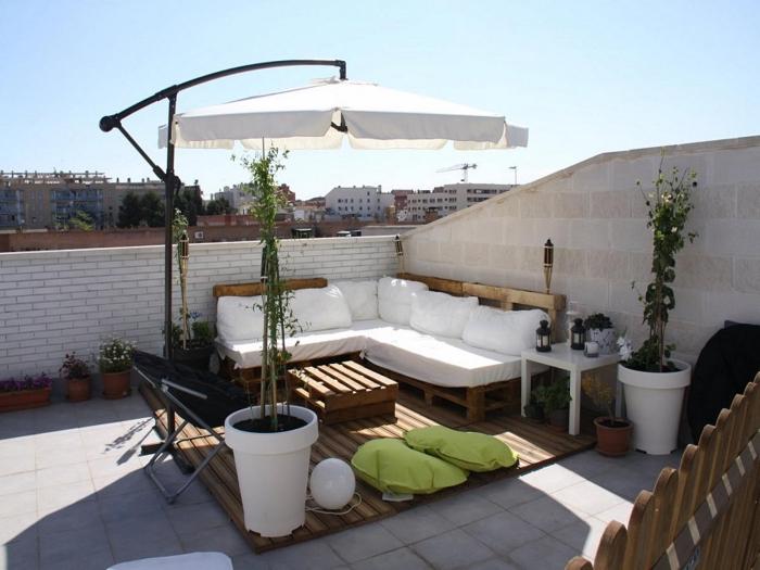 idée comment transformer une terrasse ou balcon avec mobilier en bois recyclé et plantes vertes, modèle de canapé d'angle