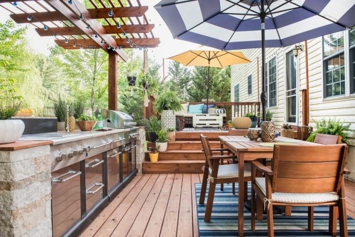 jolie décoration d'extérieur avec parasol colorés et meubles de jardin en bois foncé, modèle de cuisine en acier inox