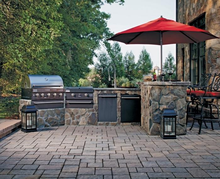 déco de jardin avec coin de cuisine en ilot pierre et équipement d'inox, modèle de chaises en fer forgé avec parasol rouge