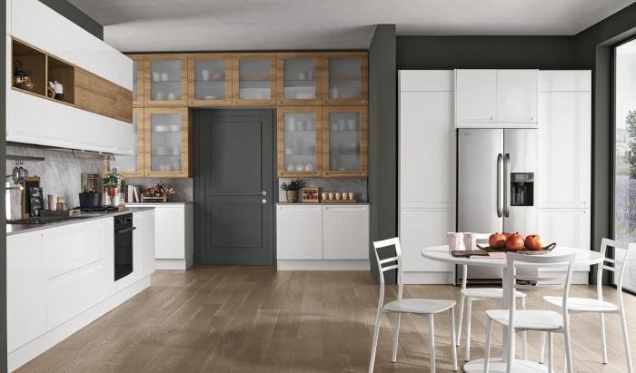 déco moderne dans une cuisine aménagée en blanc gris et bois avec coin salle à manger et grande fenetre