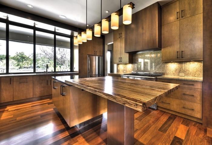 modèle de cuisine design bois foncé aux grandes fenêtres et plafond haut avec éclairage led et meubles foncés