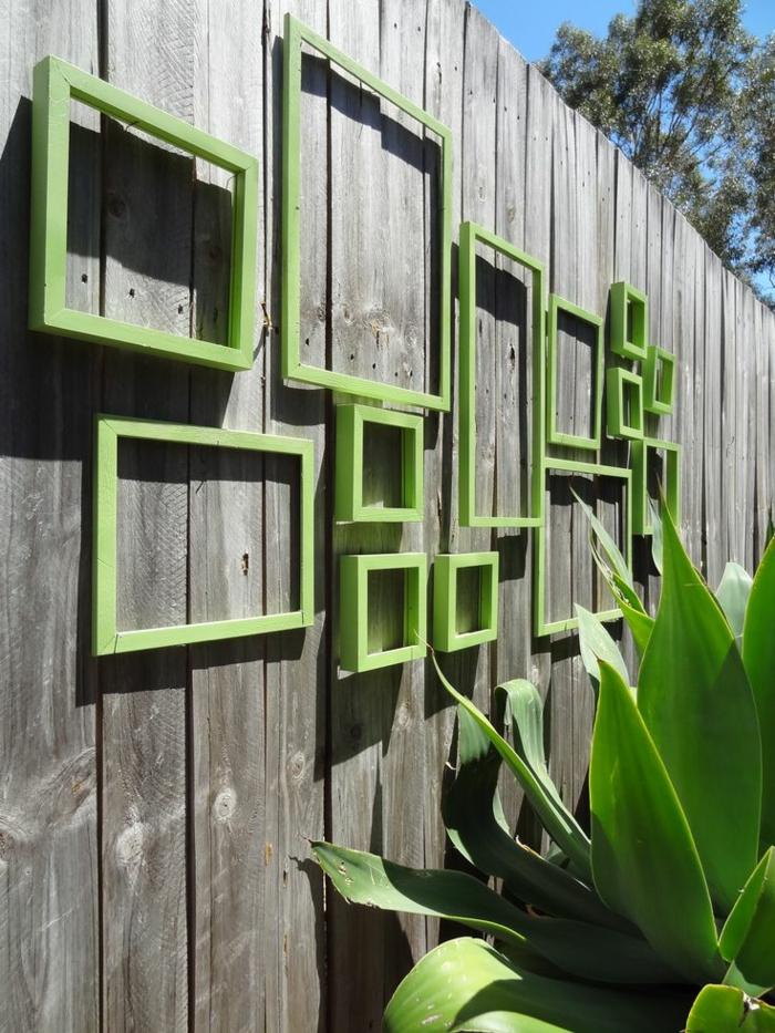 habillage mur exterieur avec des vieux cadres de tableaux repeints en vert réséda, clôture de jardin en bois gris avec effet vieilli, grande plante verte exotique