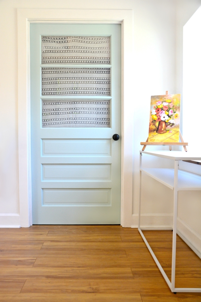 une porte d'intérieur vitrée au look vintage recouverte de petit rideau en dentelle et repeinte en vert d'eau très clair