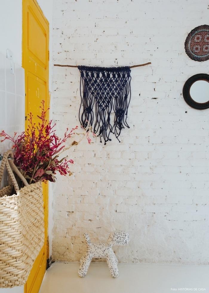 la porte d'intérieur jaune moutarde crée un contraste saisissant avec le mur en briques blanche et la déco bohème chic