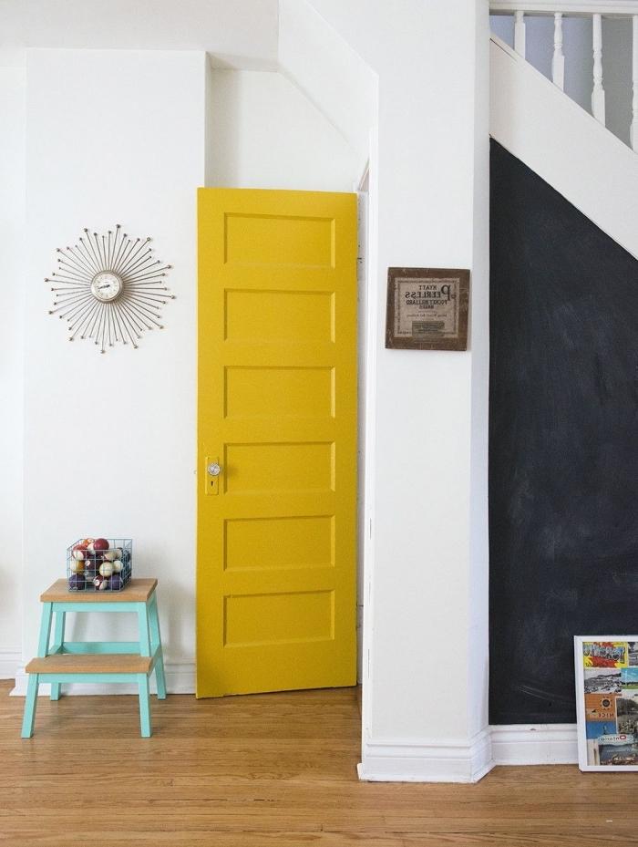 hall d'entrée original dans lequel on a crée des points colorés distincts, la porte interieur peinte en jaune et l'espace sous-escalier en peinture ardoise créent un effet de contraste avec les murs blancs