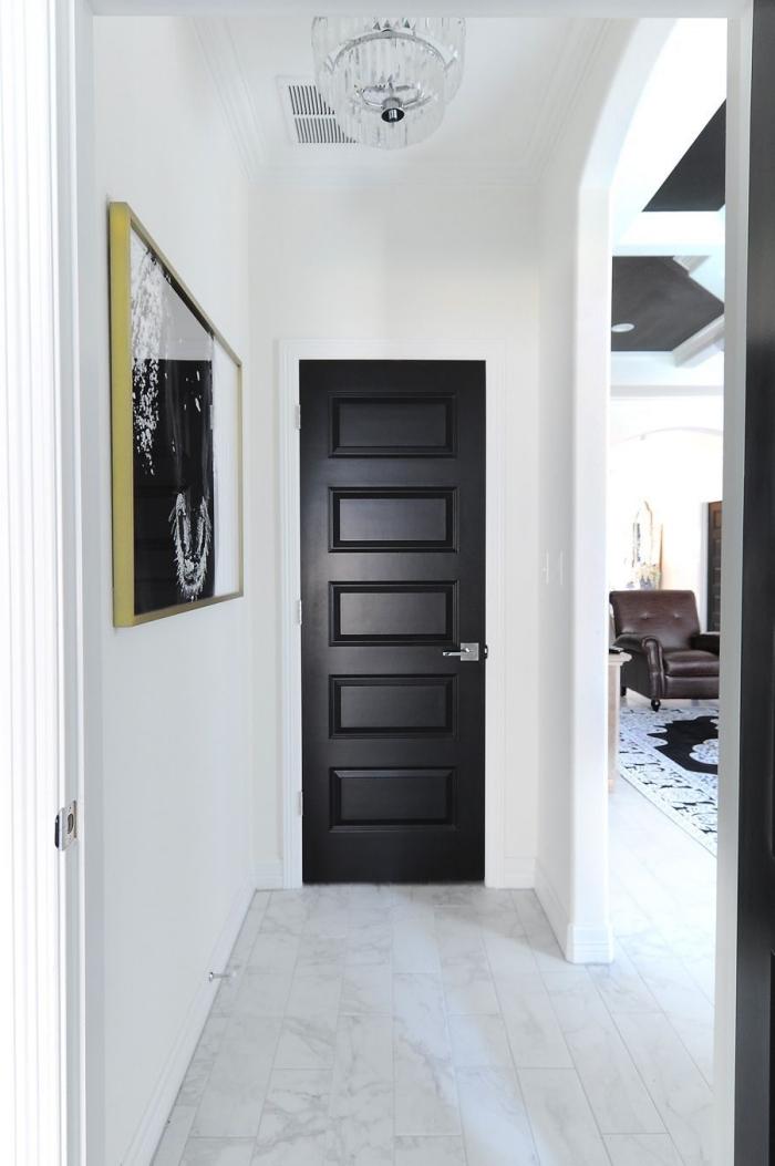 une porte d'intérieur en noir mat et une photo encadrée noir et blanc dynamise l'ambiance monochrome du couloir