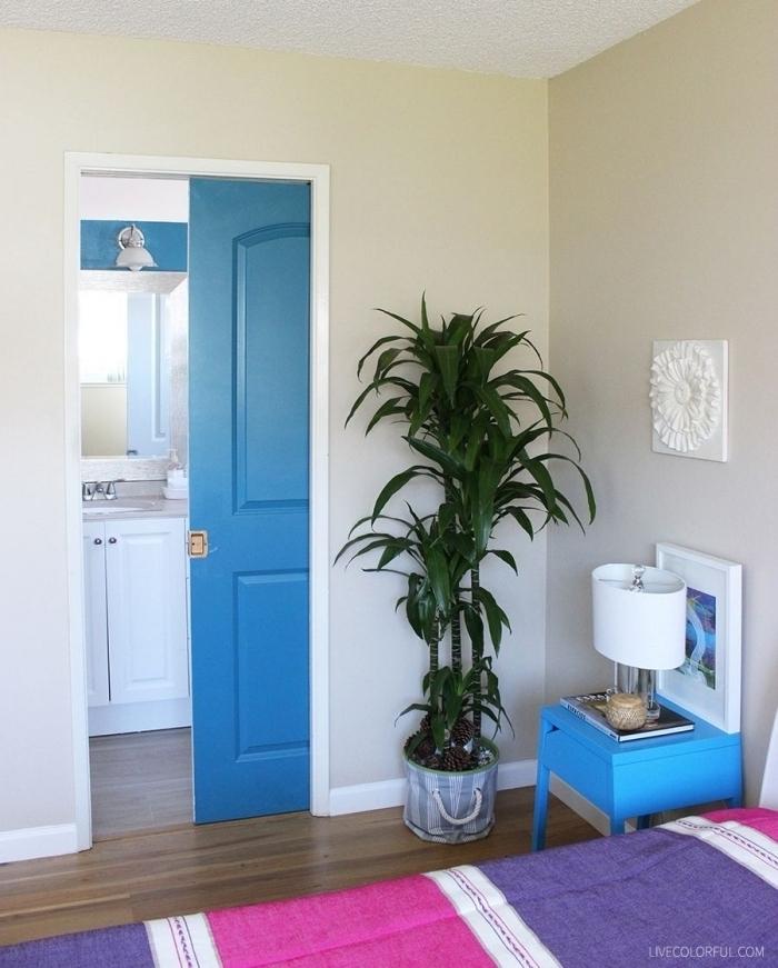une porte d'intérieur peinte de même couleur bleu marine que la table de chevet, qui apporte du dynamisme à la chambre à coucher en tons neutres