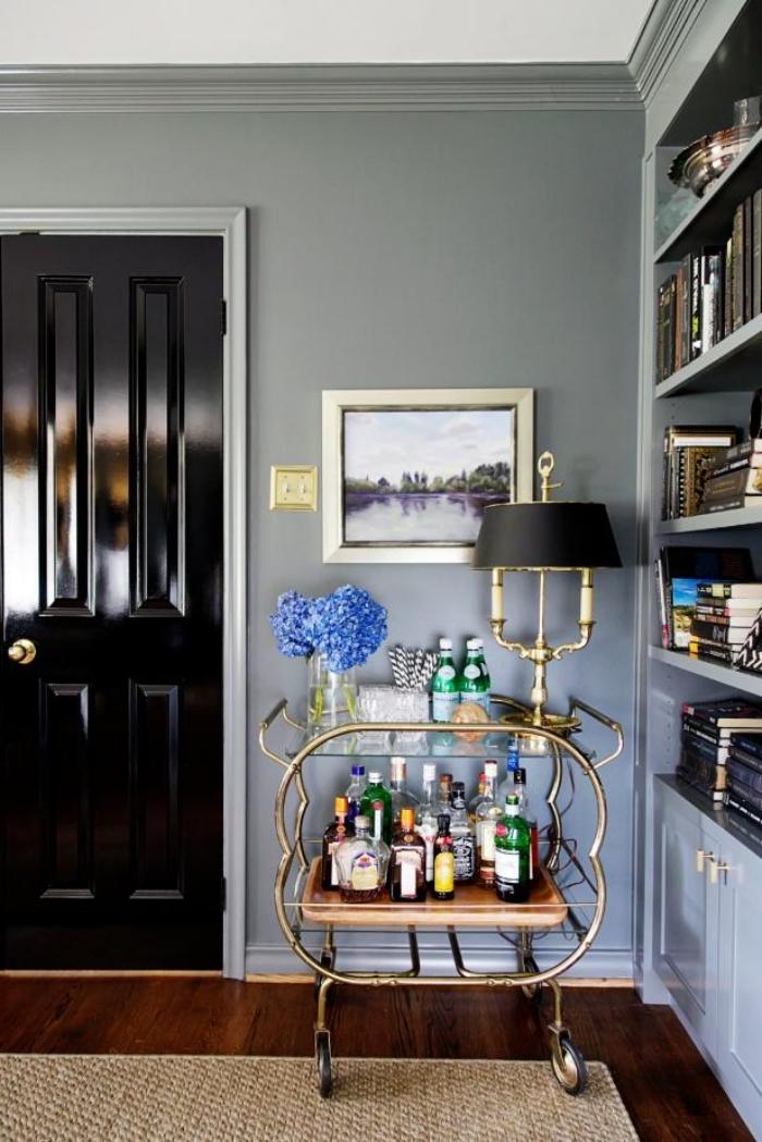 salon chic aux accents noir et dorés avec porte d'intérieur noir brillant qui s'inscrit bien dans l'ambiance élégante