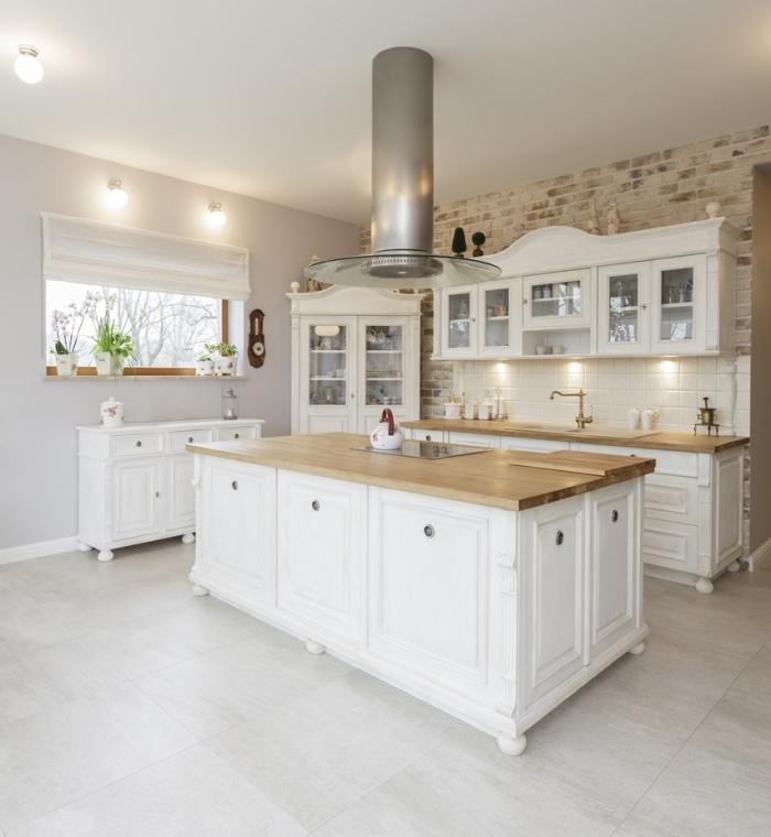 idée décoration dans une cuisine bois blanc avec pan de mur en revêtement papier peint design briques et carrelage sol gris clair
