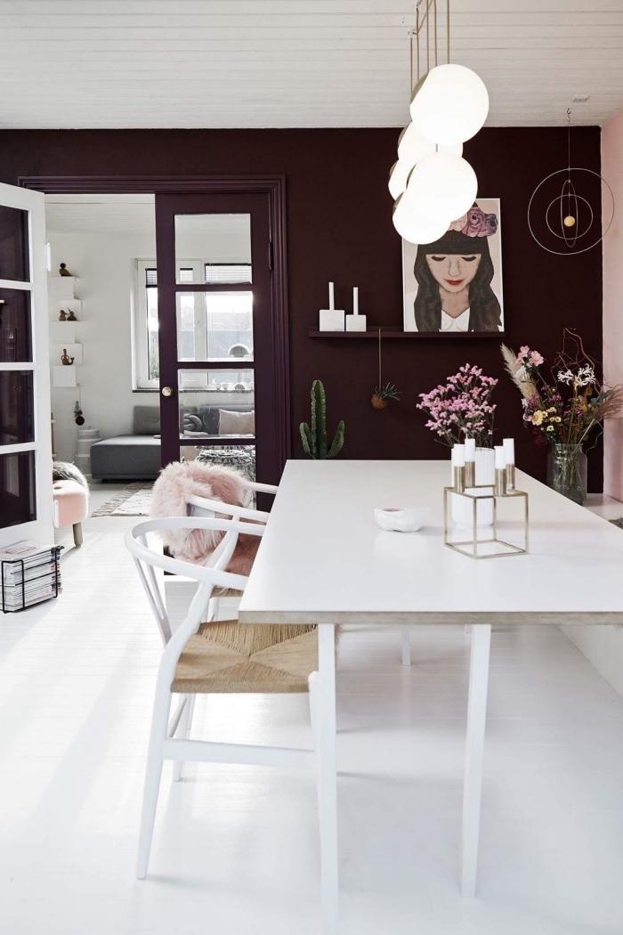 une porte interieur vitrée qui sépare le salon de la salle à manger, peinte de la même couleur que le mur aubergine