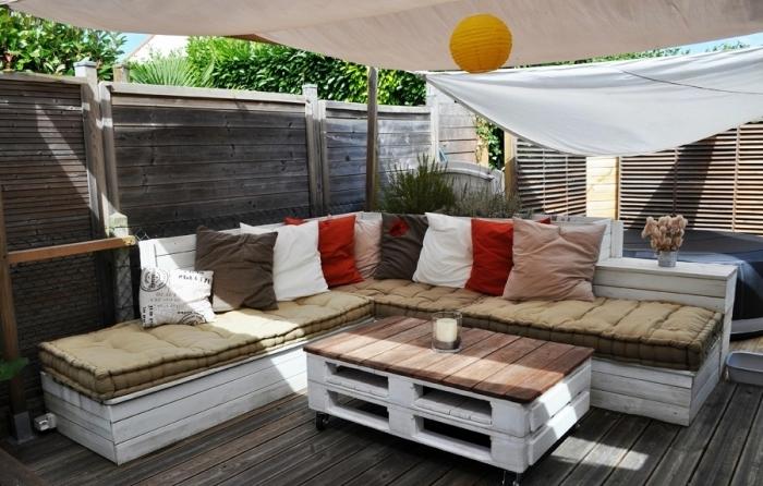ambiance déco oasis avec mobilier de bois peint en blanc, modèle de table basse en palette et canapé d'angle