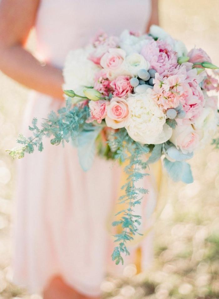 robe de mariée rose pâle, bouquet de fleurs avec éléments verts cascades