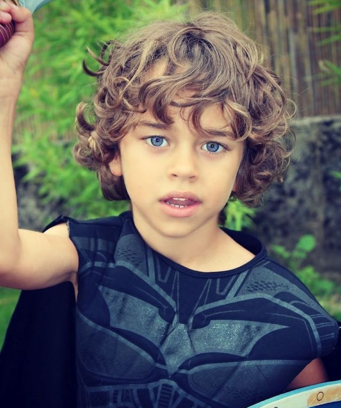 coupe cheveux enfant garçon aux boucles naturelles avec une longue frange sur le front, des yeux bleus