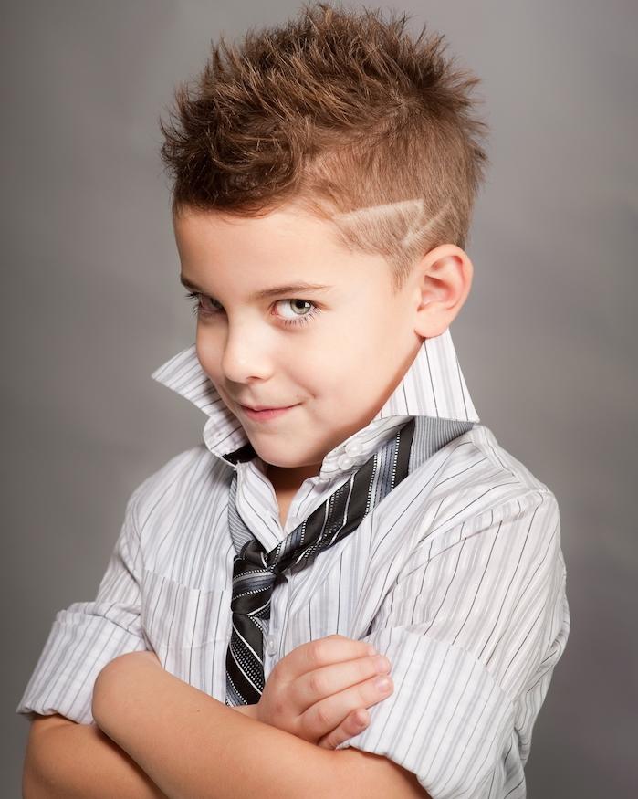 chemise gris et blanc, cravate noir et gris, cheveux hérissés en haut et cotés rasés avec une figure
