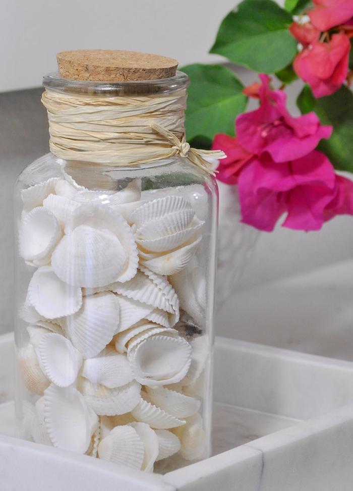 idée d activité manuelle ado avec fiole en verre remplie de petites coquilles blanches dans une assiette blanche, fleur fuchsia à coté