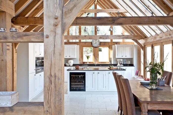 rangement cuisine bois et blanc au plafond haut avec poutres de bois et colonnes bois intérieur, idée déco style rustique dans cuisine et salle à manger