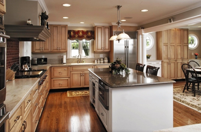 décoration de cuisine aménagée en L avec meubles de bois clair et parquet au bois marron foncé avec ilot central