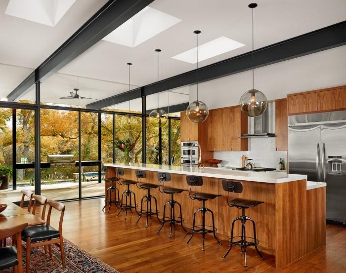modele de cuisine moderne au plafond blanc et parquet marron foncé avec ilot central blanc et bois marron