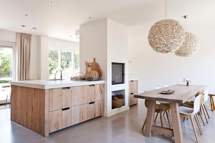 déco de cuisine blanc et bois aux murs blancs et sol gris clair avec ilot central en bois massif et comptoir blanc