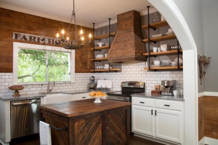ambiance rustique dans une cuisine aux murs en revêtement bois foncé et crédence au carrelage briques blanches