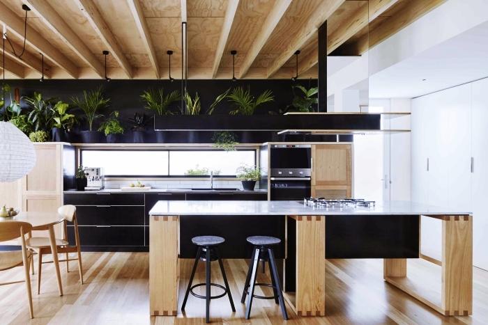 aménagement de cuisine moderne en bois avec plafond en poutres de bois clair et pan de mur en noir mate, décoration avec plantes vertes