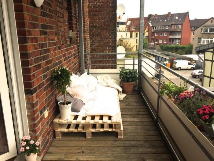idée comment aménager son balcon au sol de bois foncé et murs en briques rouges avec un mobilier en palettes