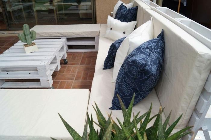 coin extérieur au carrelage de sol marron aménagé avec meuble de palettes blanc, table basse en palette avec cactus