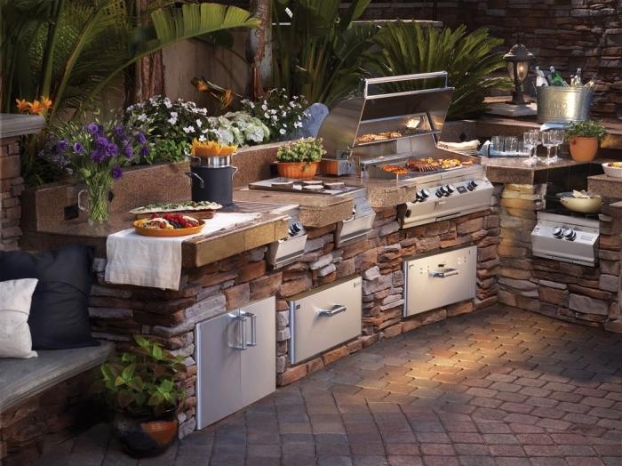 modèle de cuisine de jardin avec ilot en pierre et plan de travail en matériel résistant, déco de jardin avec coin de repos en banc