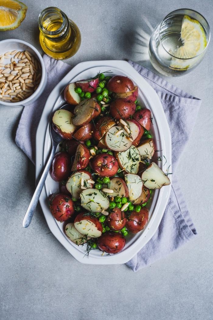 salade d'été originale pour accompagner un barbecue, de pommes de terre à peau rouge sautées au beurre et à l'aneth, pois, et pignons de pin grillés