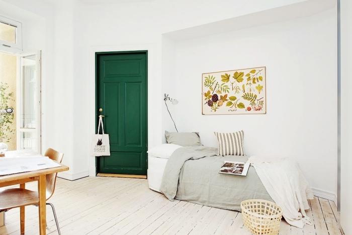 une porte chambre à coucher scandinave peinte en vert sapin contrastant avec la déco épurée, une déco chambre à coucher scandinave qui fait allusion à la nature
