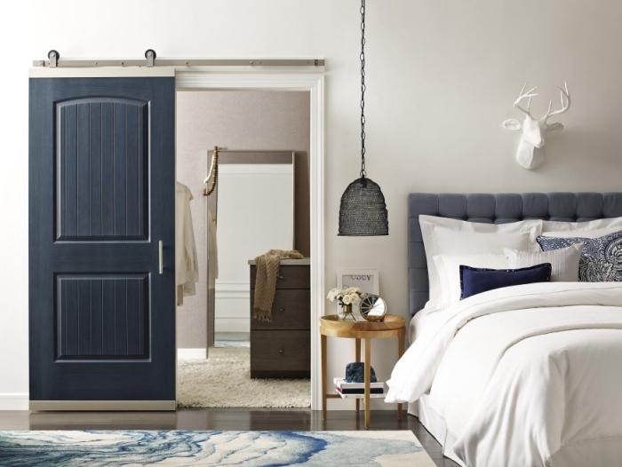 une porte interieur coulissante peinte en bleu nuit qui constitue un accent chic dans cette chambre parentale élégante et sereine