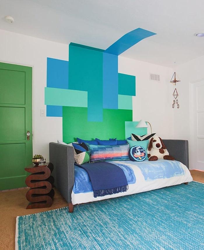 intérieur vintage aux nuances du bleu et du vert plein de fraîcheur, dynamisé par la porte d'intérieur couleur vert sapin mat et la peinture murale graphique
