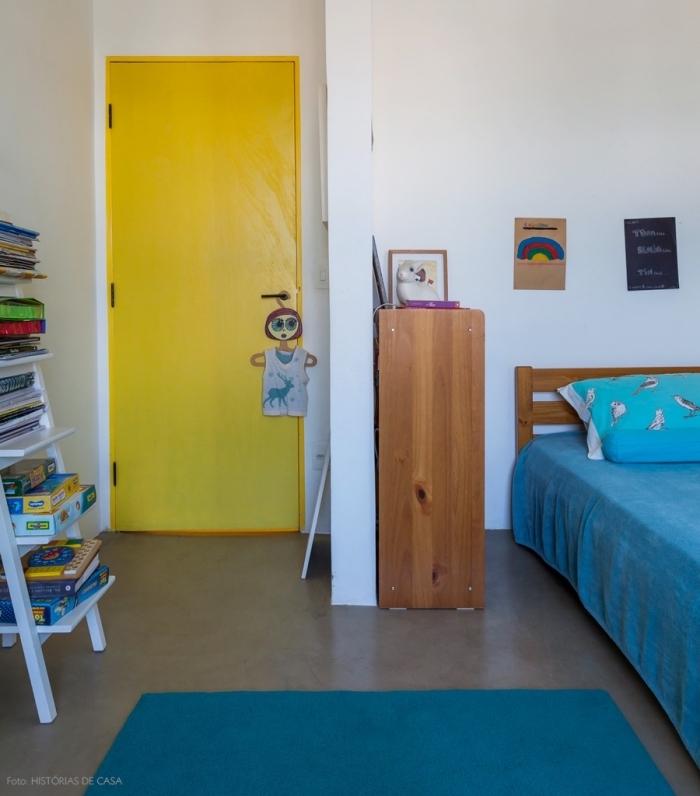 une porte chambre d'enfant peinte en jaune fluo qui dynamise l'intérieur blanc de paire avec les touches de bleu sur le tapis et le linge de lit