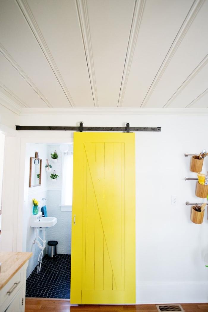une porte interieur bois de grange repeinte en jaune fluo qui délimite la salle de bain et contraste avec les mures blancs et le carrelage noir