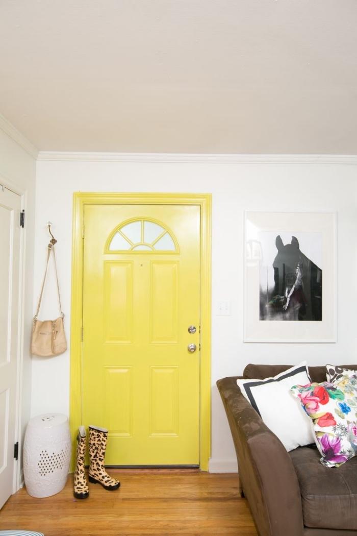 une porte d'intérieur jaune fluo et un poster mural noir et blanc pour une ambiance contemporaine dans le salon