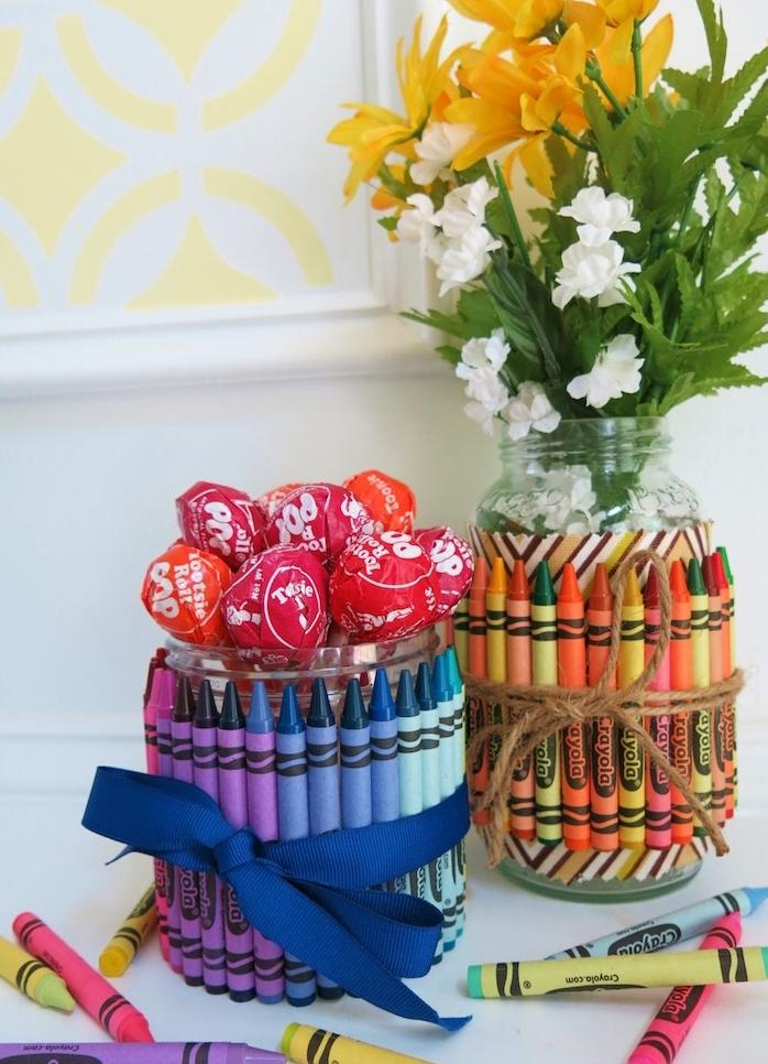 vase ou récipient bonbons avec sucettes dans un bocal en verre décoré de crayons en couleur et ruban, cadeau merci maitresse simple a fabriquer soi meme
