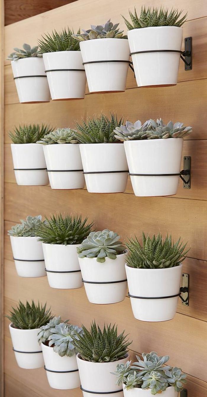deco mur exterieur, habillage mur exterieur, comment habiller un mur exterieur avec des porte-plantes en métal noir étagères et des pots en céramique blanche avec de la végétation verte exotique basse