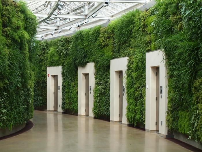 mur végétalisé interieur, couloir entièrement en vert, végétation sur tous les murs, quatre ascenseurs aux cadres en pierre blanche, toit en verre transparent en style orangerie