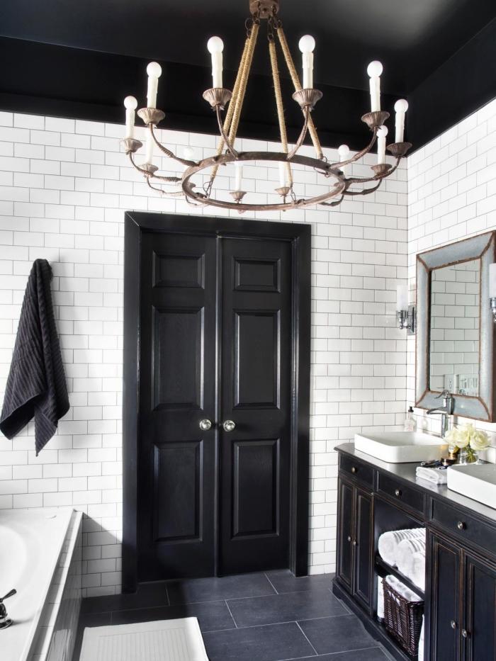 une salle de bains en total look noir et blanc avec une porte interieur double peint en noir en joli contraste avec le carrelage métro