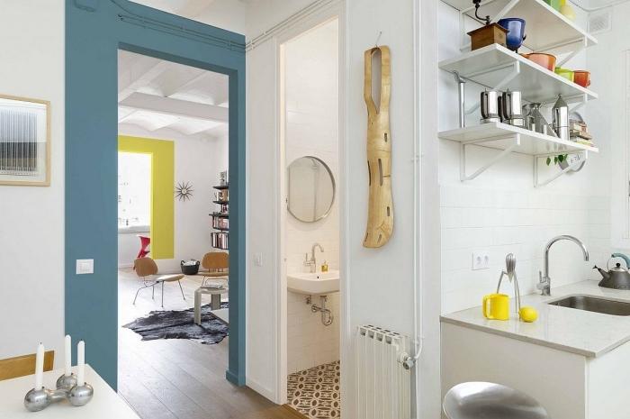 des cadres de peinture bleu et jaune autour de la porte et de la fenêtre dynamisant l'intérieur blanc, quelle couleur peindre encadrement porte pour en fair un élément décoratif