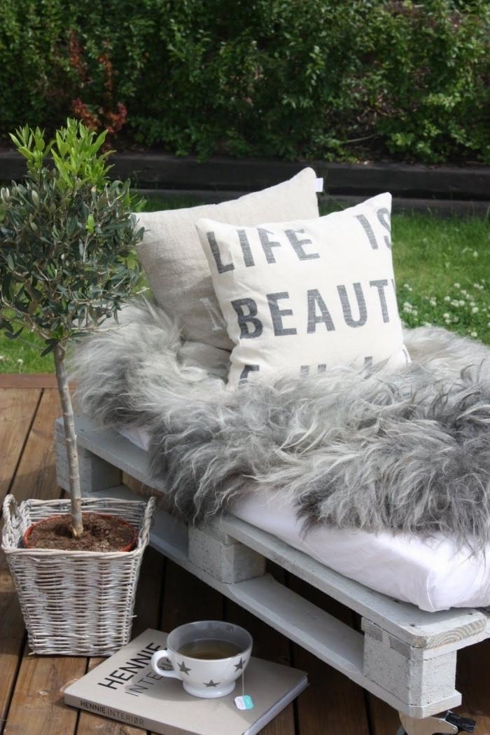 accessoires de style cocooning pour décorer un coin de repos extérieur avec meuble en palette et plantes vertes