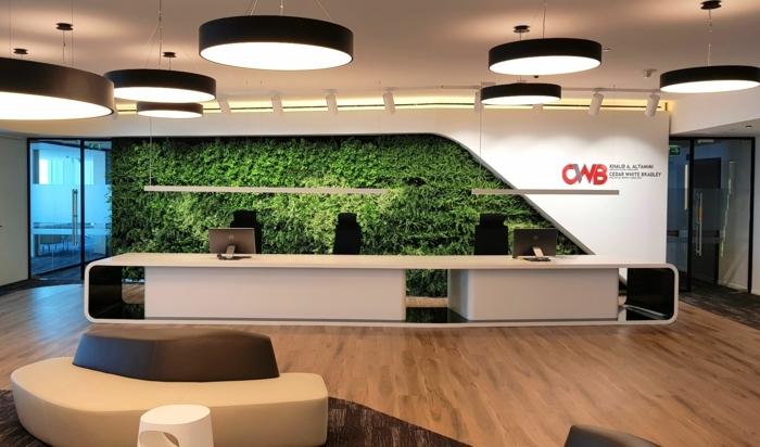 culture verticale derrière un bureau de réception, grands spots luminaires au plafond en forme de tambour, mur végétalisé, sol recouvert de parquet PVC aux motifs boisés