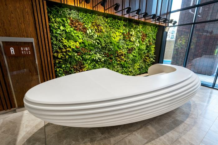 mur végétal intérieur, hôtel, réception avec grand meuble ovale blanc au design futuriste, mur végétalisé illuminé par des spots luminaires en métal noir