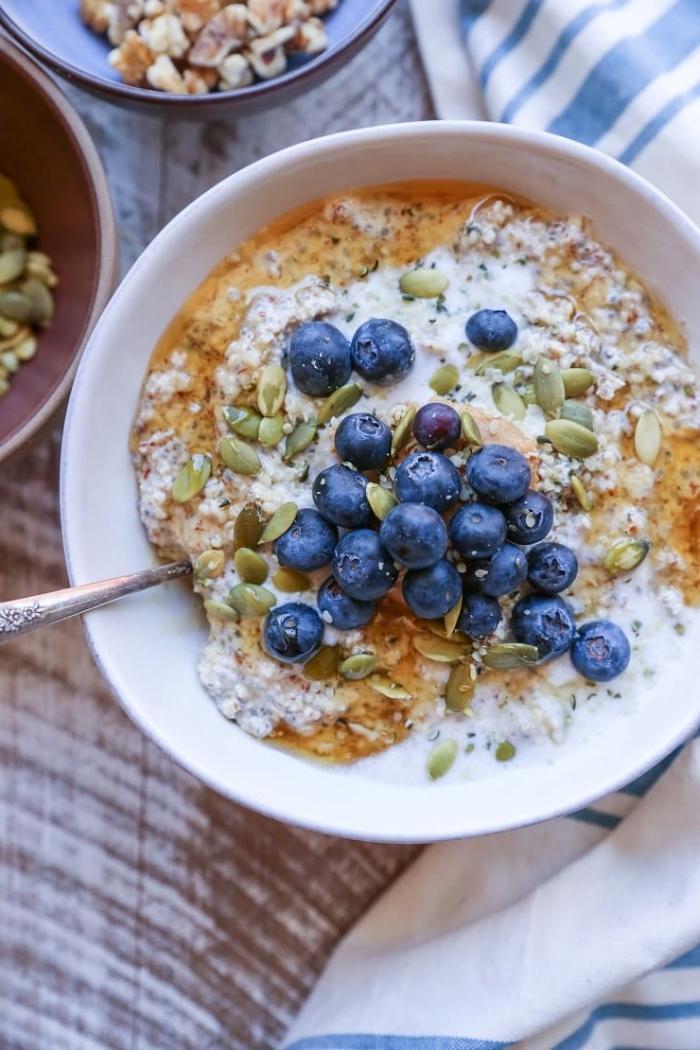un bol de petit déjeuner vegan et rassasiant de myrtilles, graines de citrouille, noix, graines de lin, recette de flocons d'avoine petit déjeuner healthy