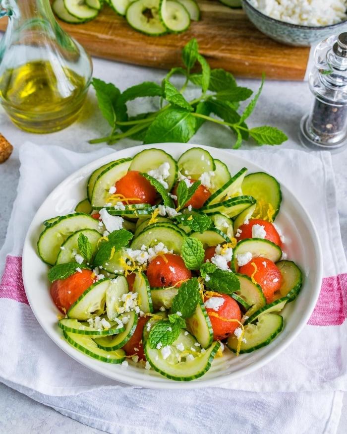 idée de salade d'été originale pour faire le plein de fraîcheur, salade de concombre en rondelles, billes de pastèque, fromage feta et feuilles de menthe
